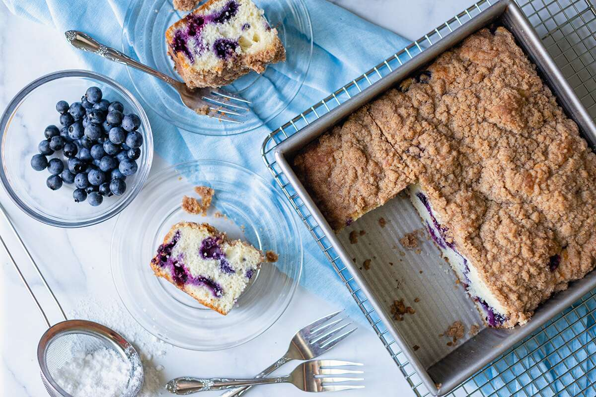 A pan of Blueberry Buckle Coffeecake with a few slices next to it on plates, along with fresh blueberries
