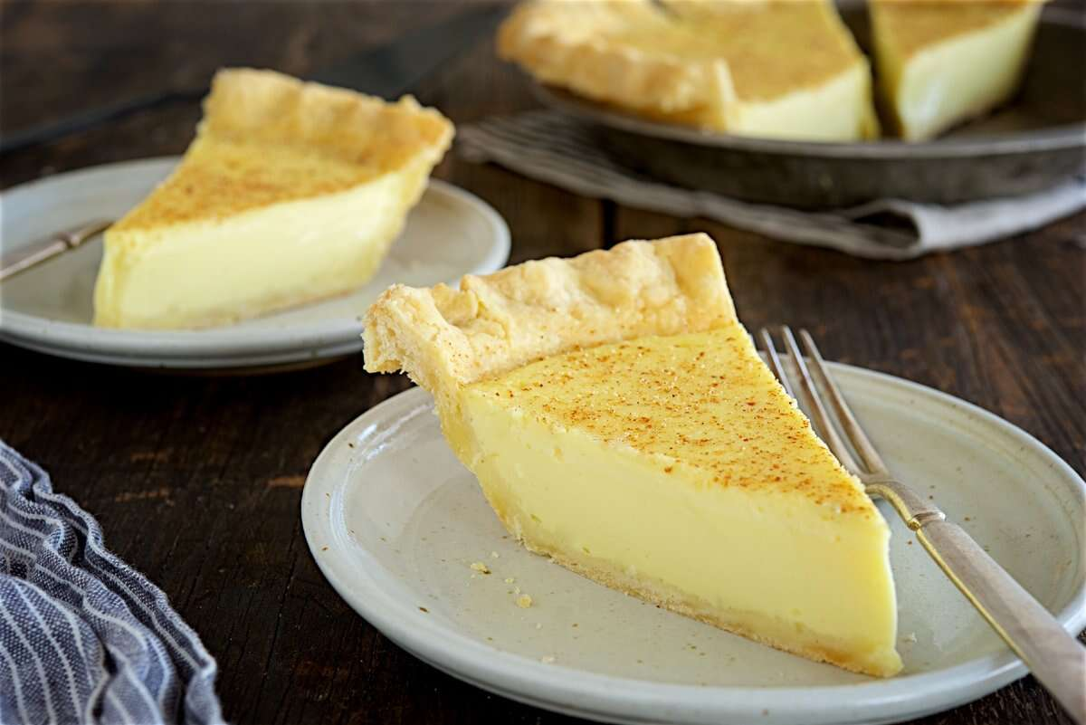 Two slices of custard pie on plates with the rest of the pie in the background