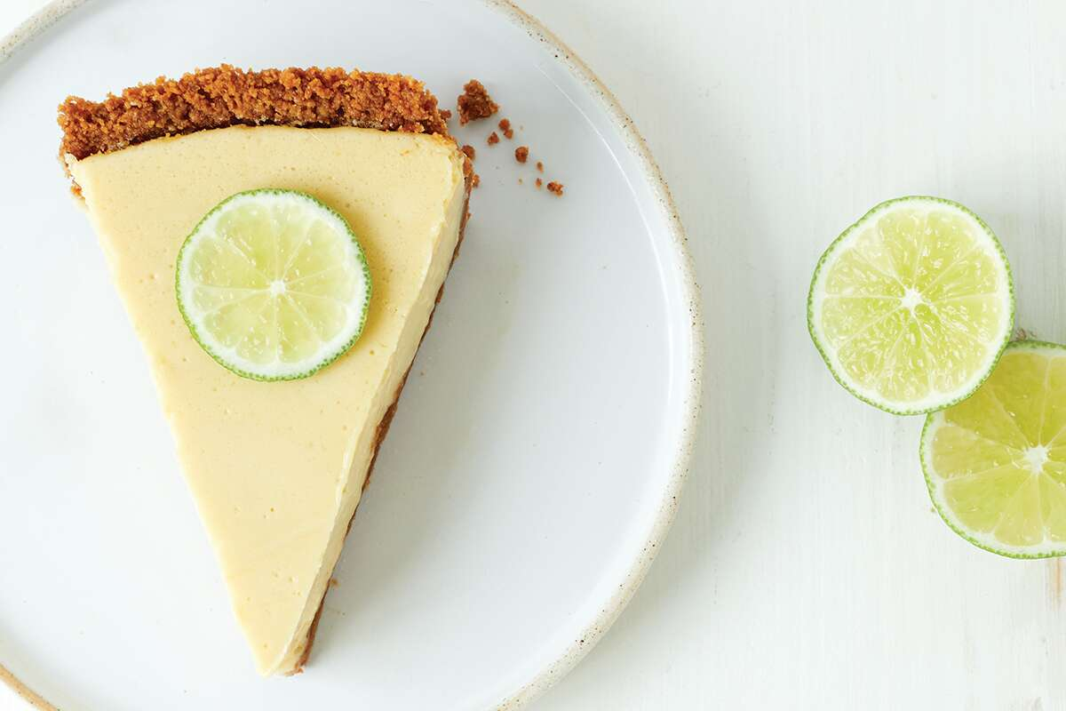 A slice of key lime pie with a graham cracker crust