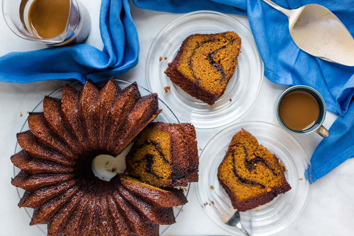 Pumpkin Espresso Bundt Cake with a few slices on plates next to a coffee