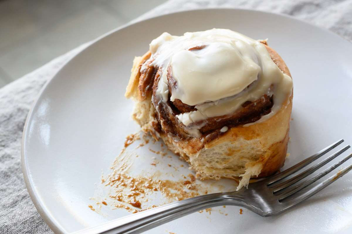 Sourdough cinnamon bun topped with icing.