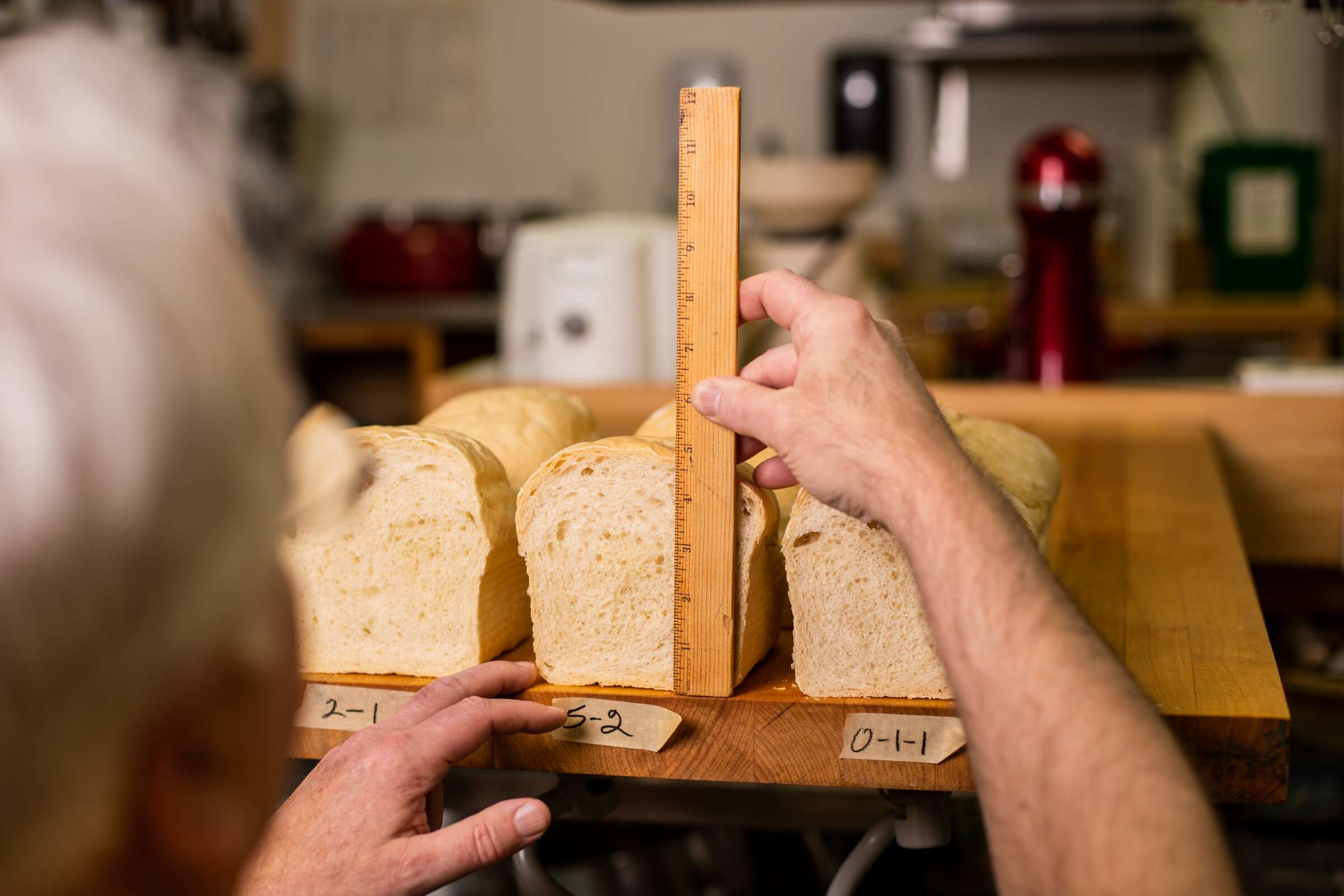 Frank measures loaves of bread in the King Arthur test kitchen