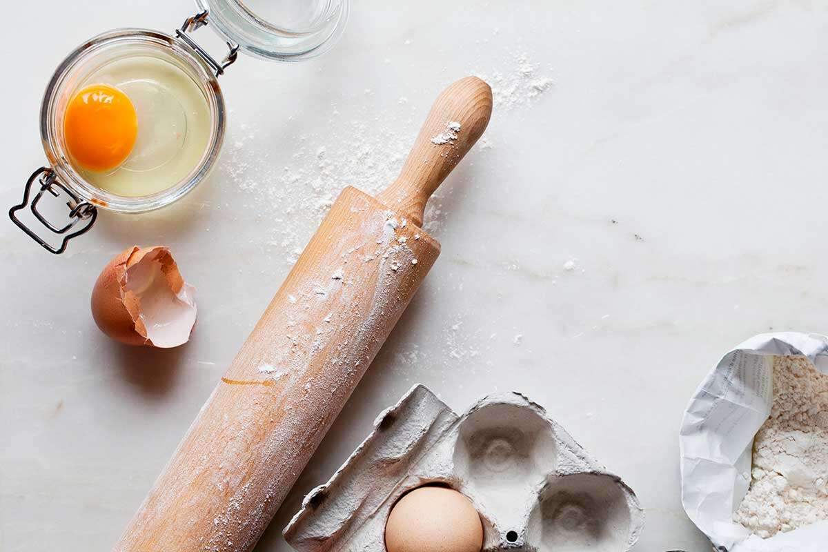 Eggs, a rolling pin, and a bag of flour on a kitchen counter