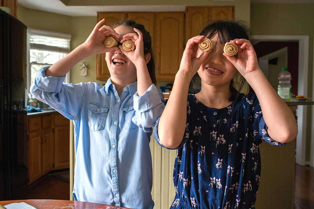 Two older kids being silly by holding cinnamon rolls up as if they were eyes