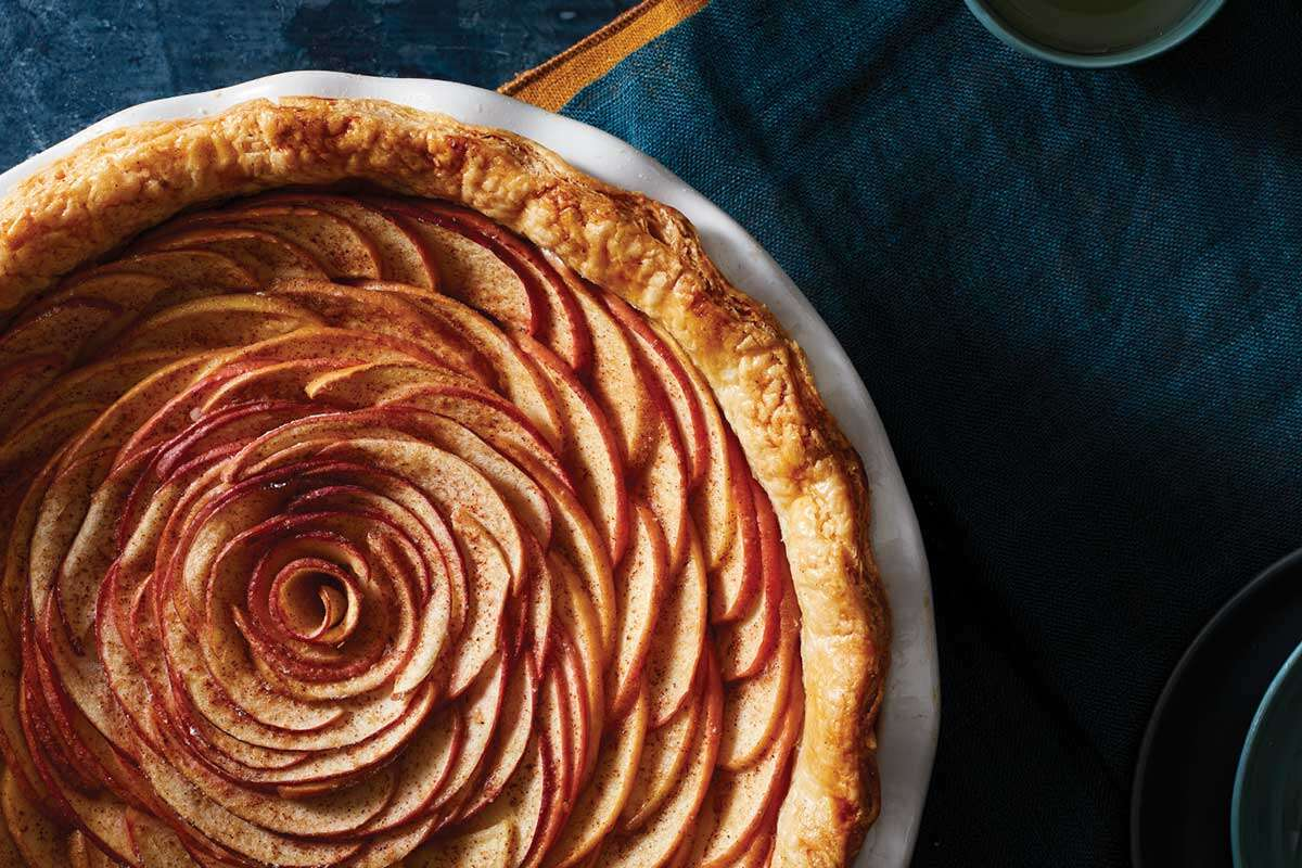 An apple pie with the apple slices arranged in a rose-like pattern