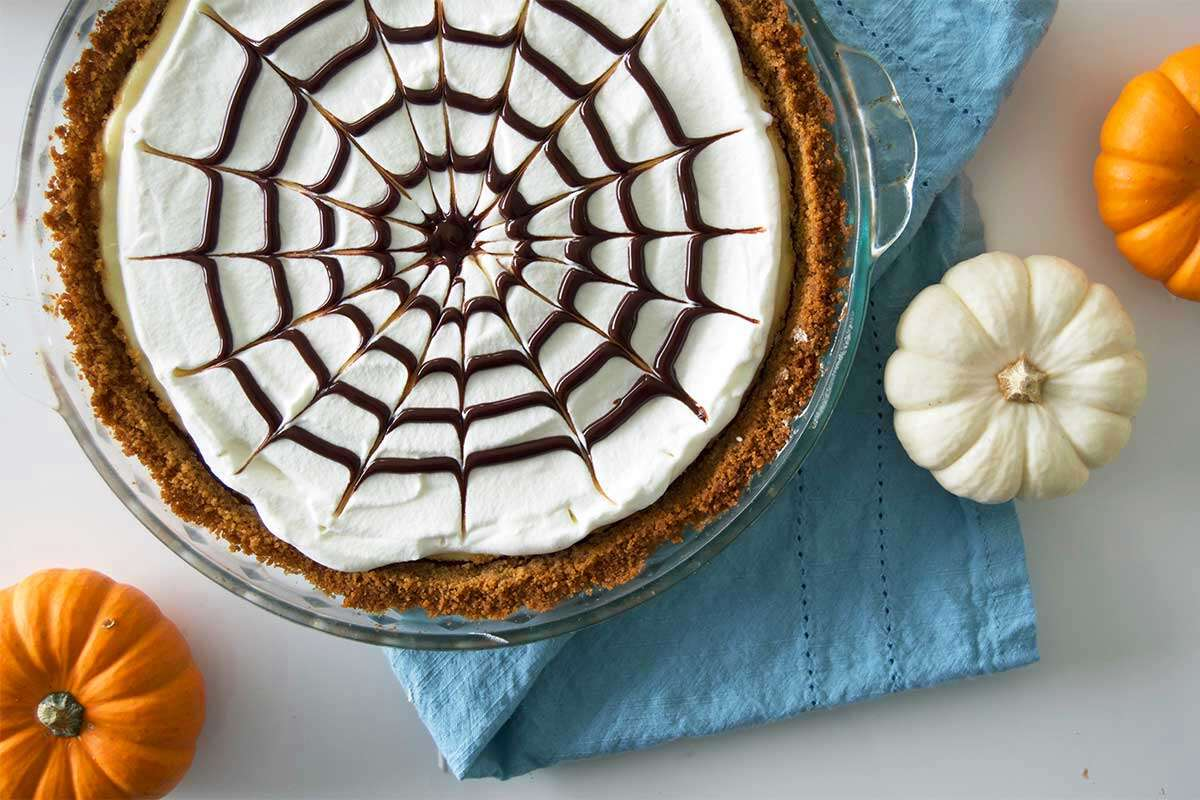 Spider web cheesecake surrounded by mini pumpkins