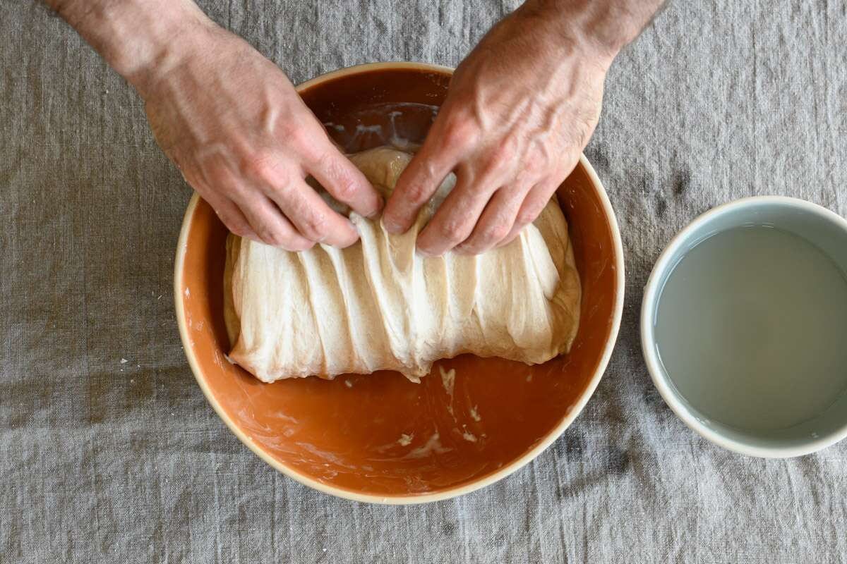 A baker folds bread dough in a bowl