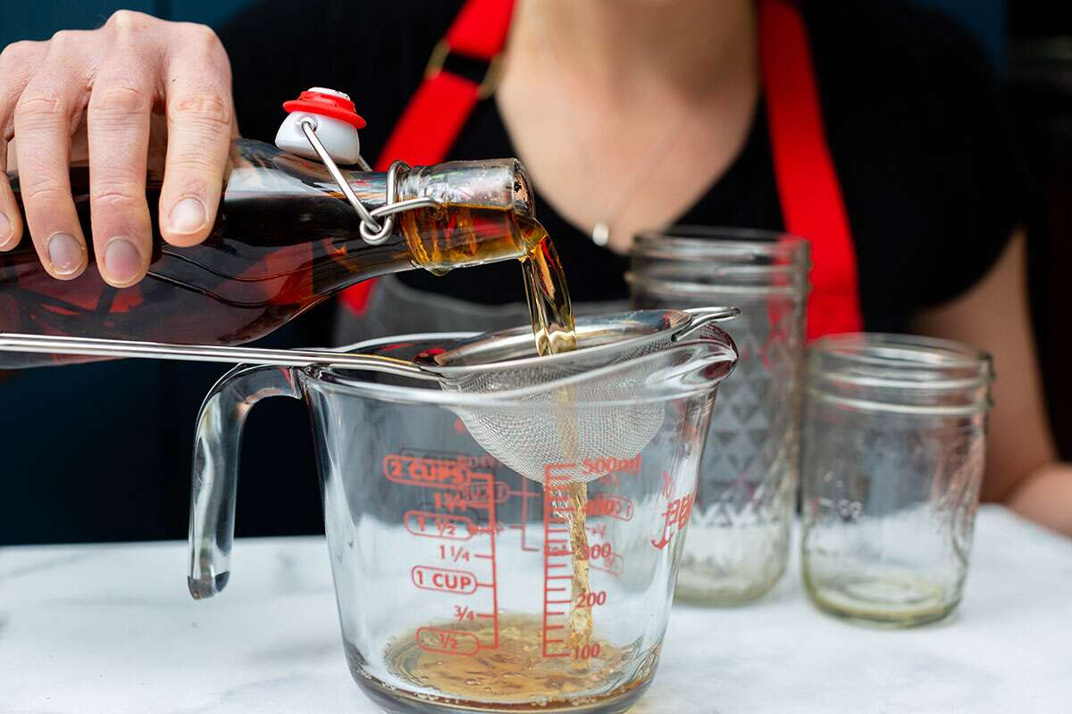 A baker pouring aged vanilla extract through a sieve into a measuring cup to filter out the vanilla bean.