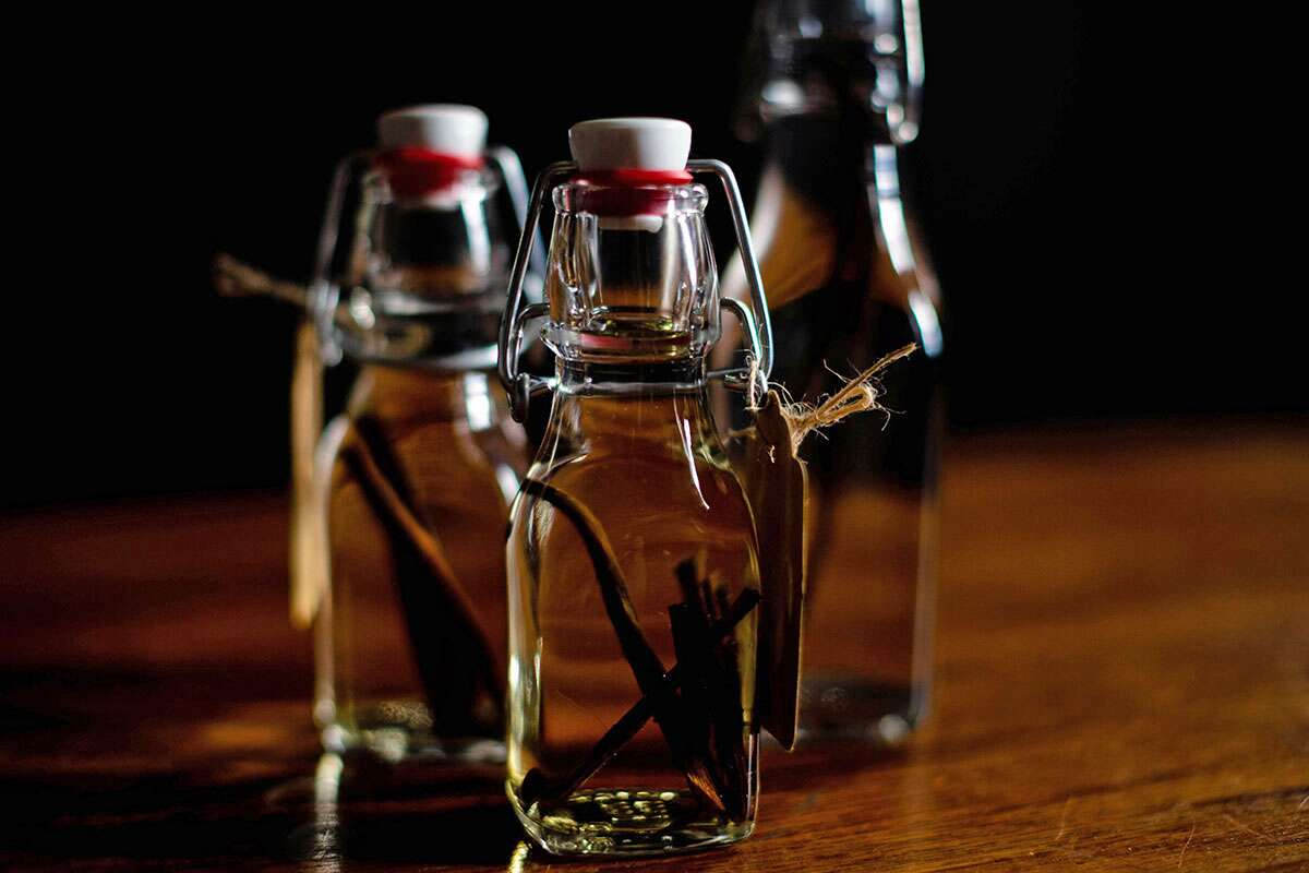 Three bottles of homemade vanilla extract, ready to infuse, placed in a cool and dark place.
