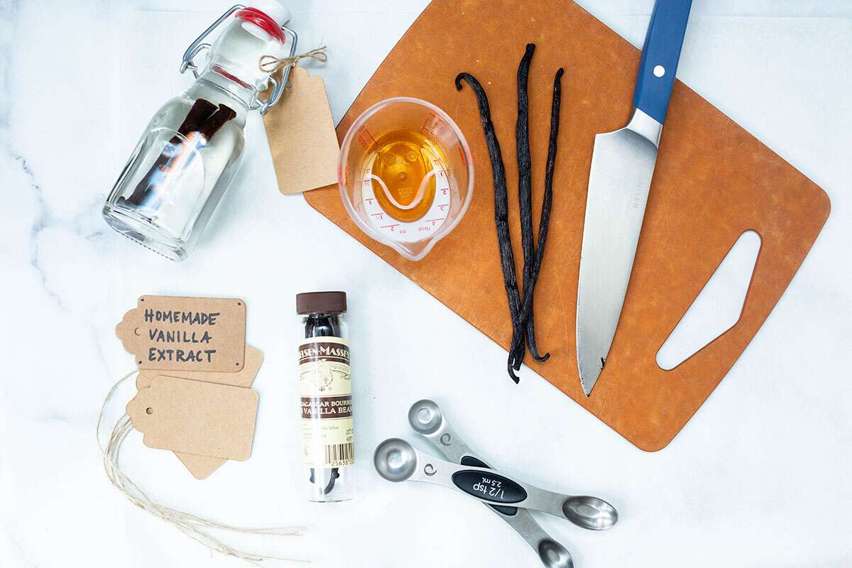 Tools and ingredients needed to make homemade vanilla extract: vanilla beans, a knife, alcohol, and a clean jar.