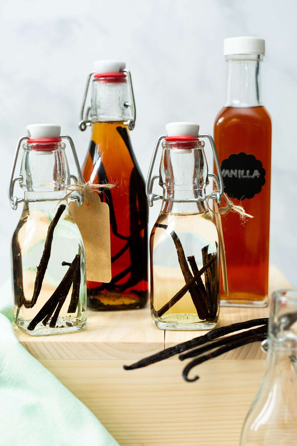 Small and large bottles of vanilla extract that have been aged for varying amounts of time, as well as a few vanilla beans.