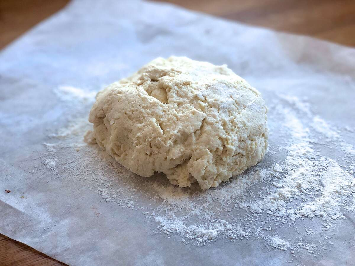 Biscuit dough on a floured piece of parchment waiting to be shaped.