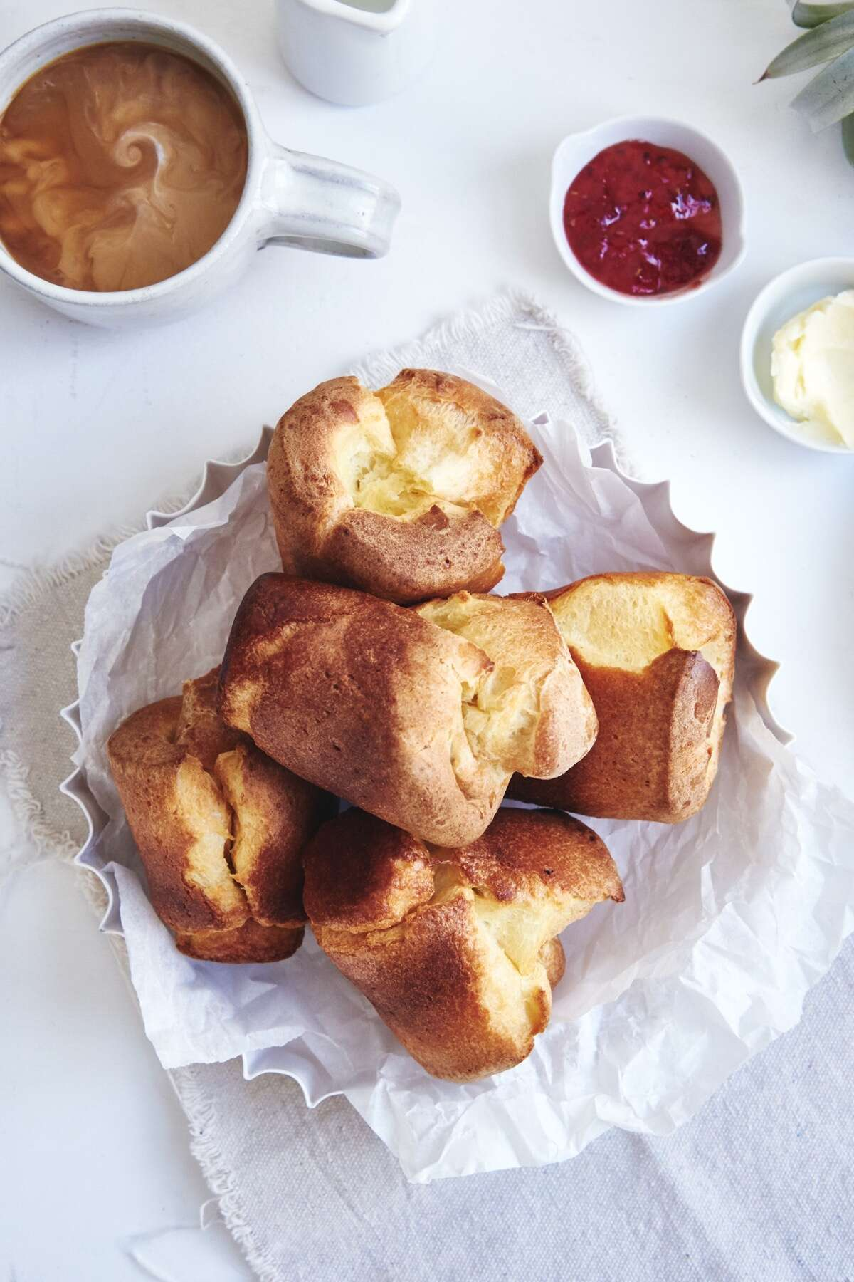 Basket of sourdough popovers on a table with jam, butter, and a latte.