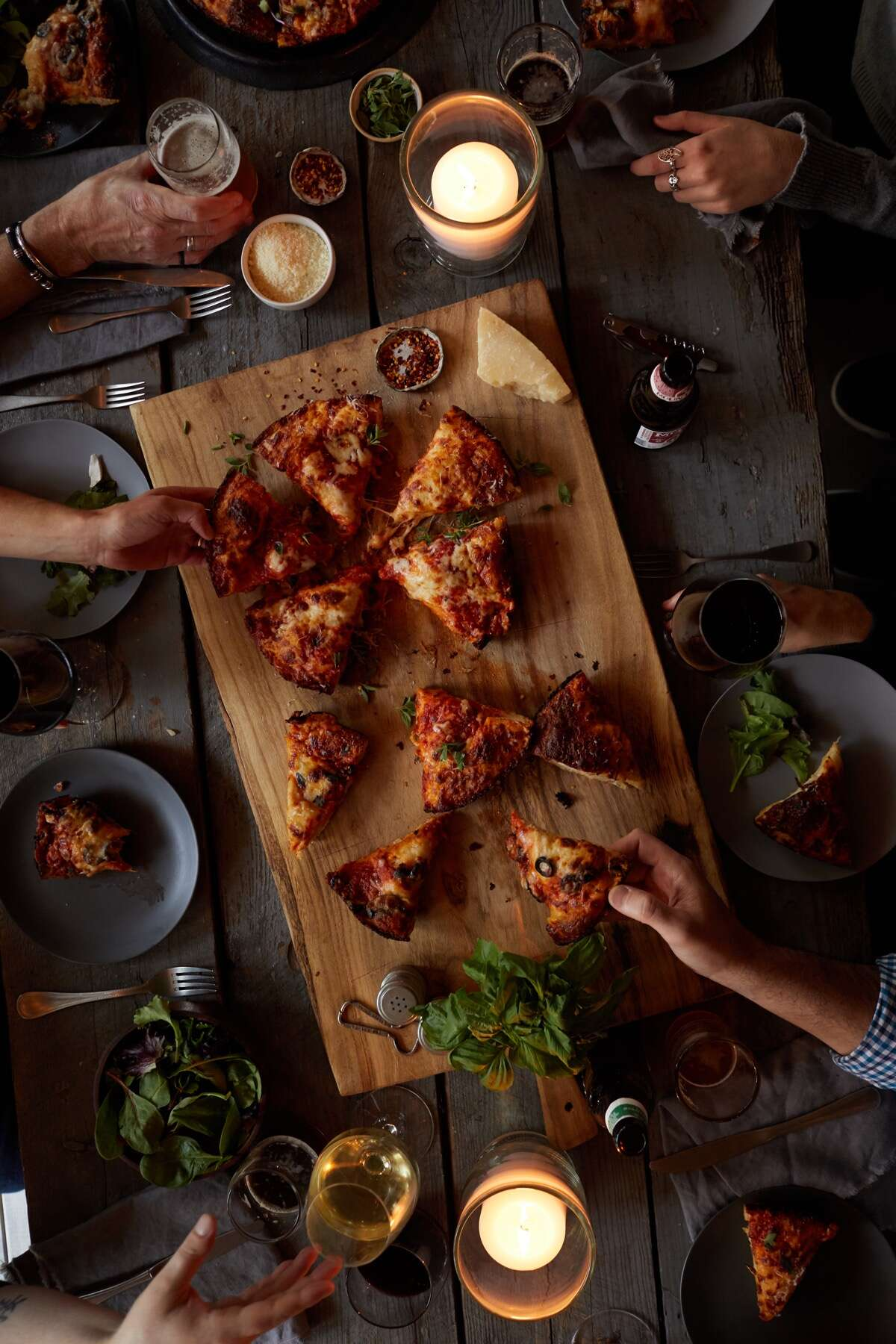 Baked pizza on a cutting board with lit candles, wine, beer, and hands of people sharing.