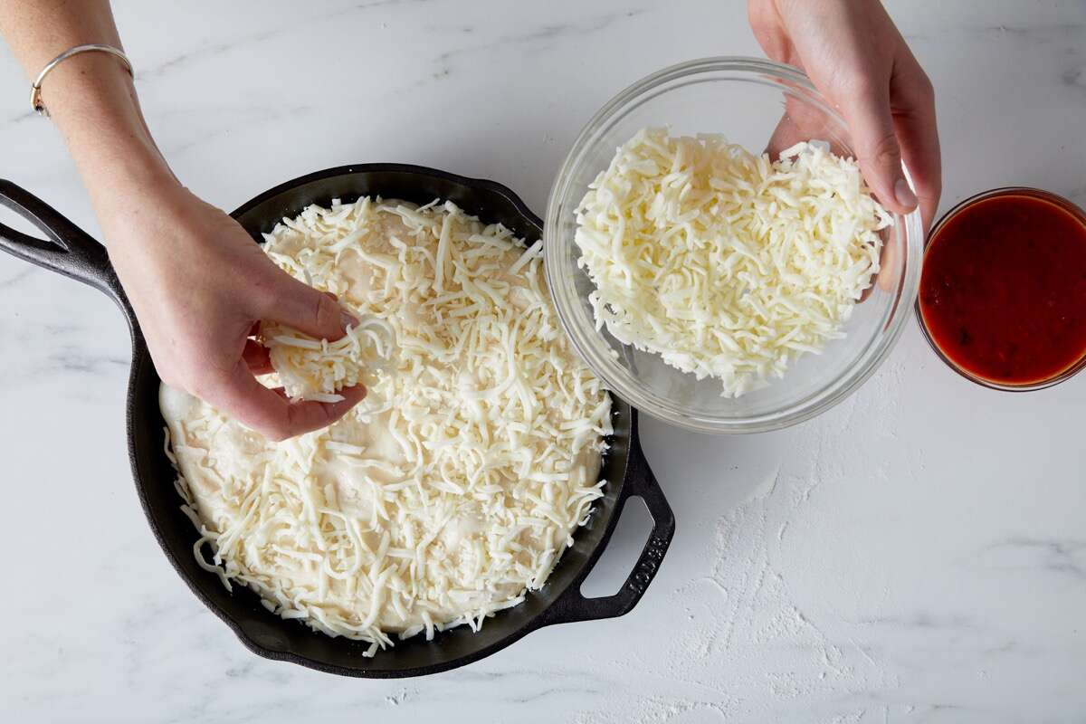 Cheese being sprinkled on unbaked pizza crust in a cast iron pan.
