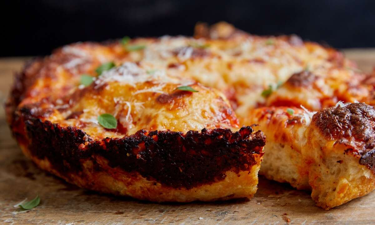 Baked thick-crust pizza showing its heavily charred cheesy edge.