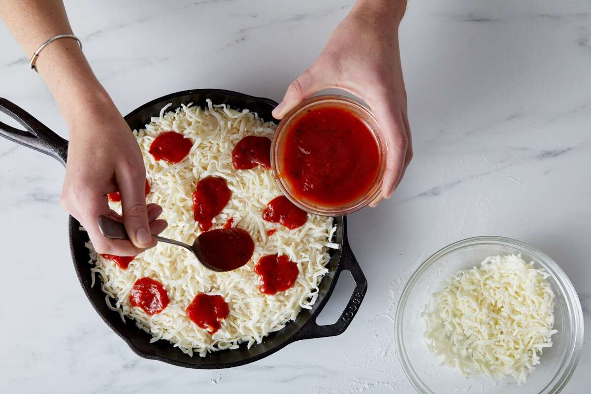 Tomato sauce being dolloped atop a cheese-topped pizza before baking.