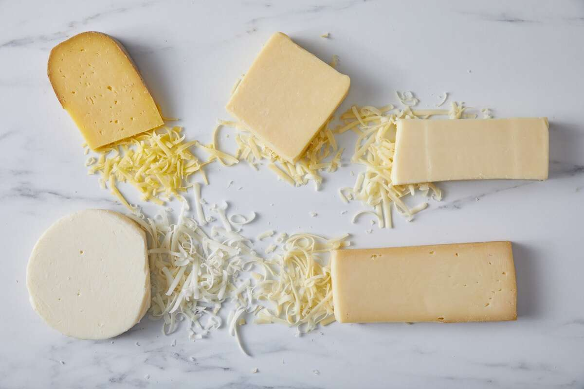 Blocks of different types of cheese on a marble slab, some grated.