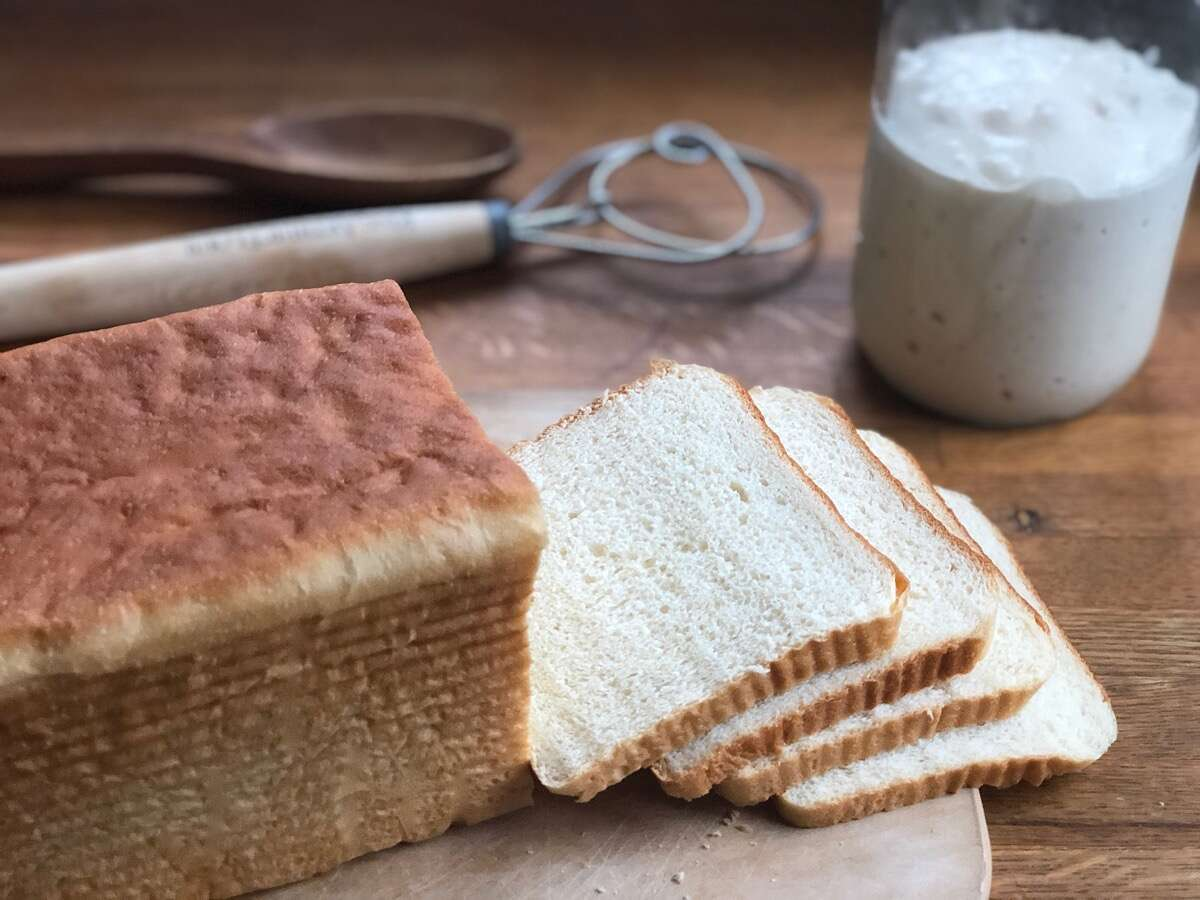 White sandwich bread from a pain de mie pan, sliced on a cutting board