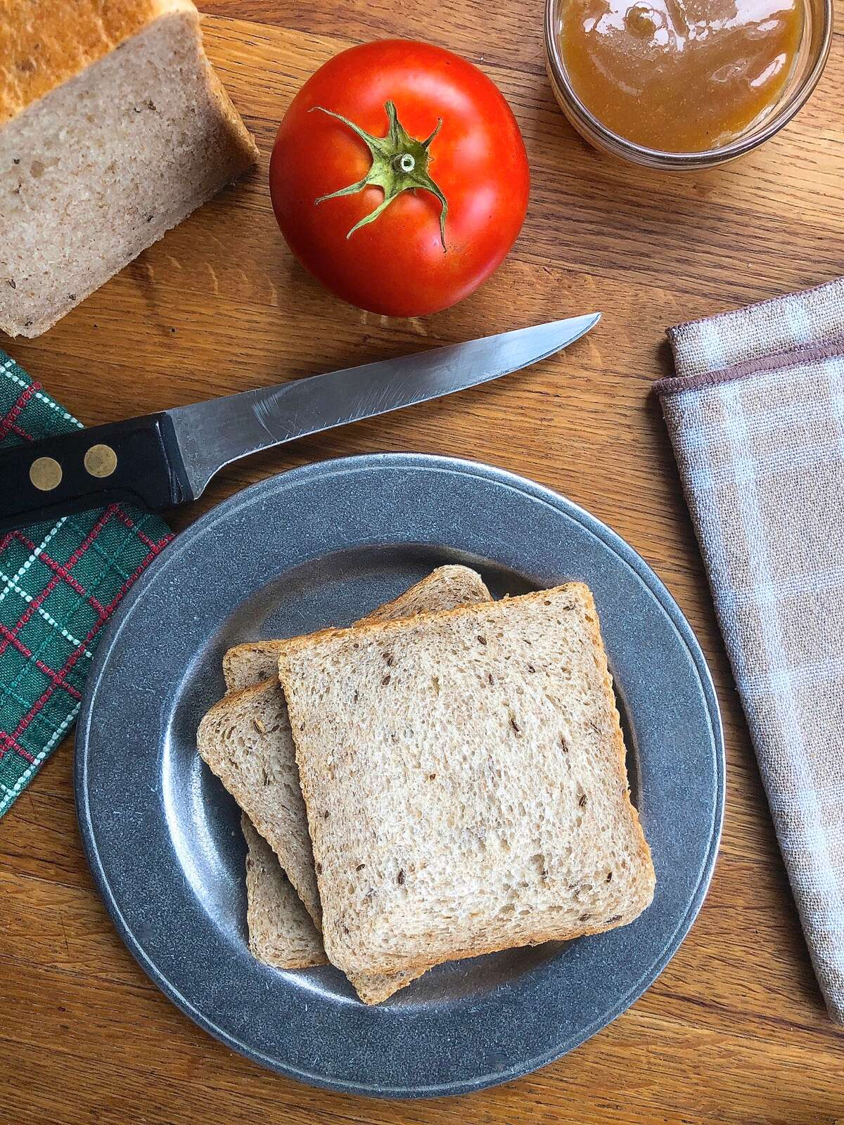 Sliced rye bread on a plate, ready to make into a sandwich.