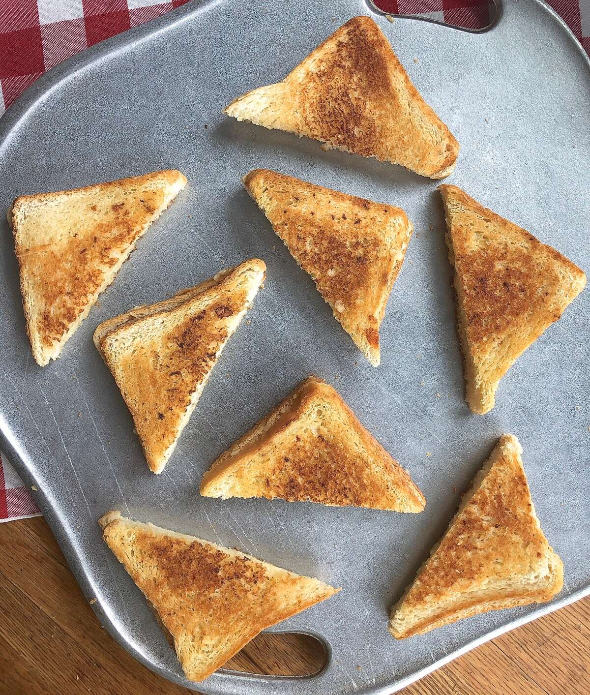 Grilled cheese sandwiches cut in triangles, arranged on a serving plate