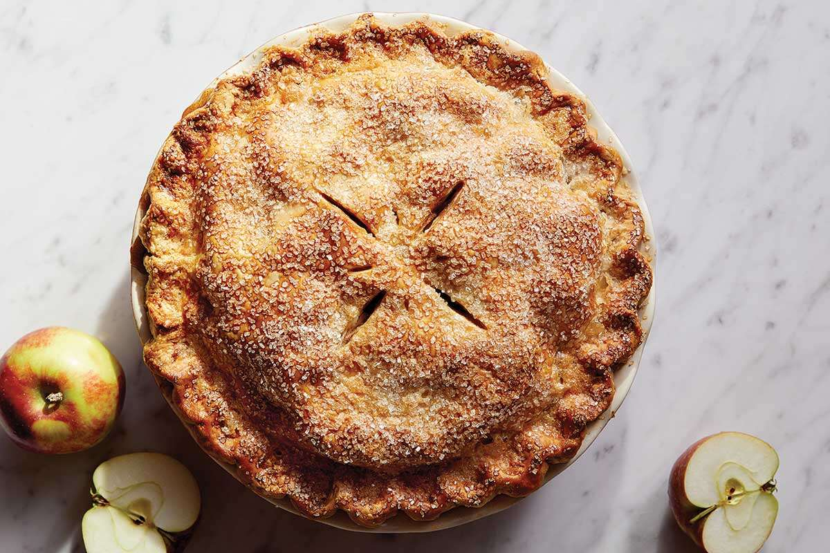 A traditional double crust apple pie topped with sparkling sugar next to a few apples