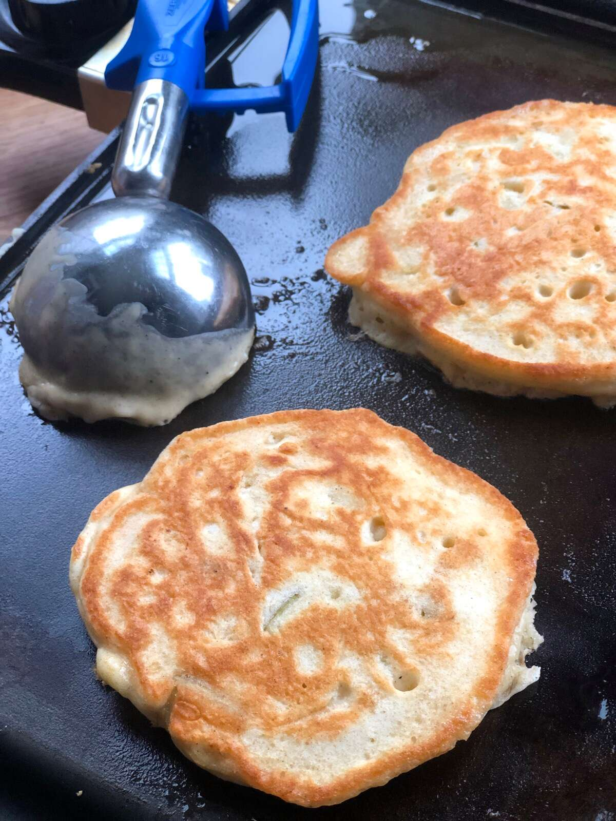 Two pancakes cooking on a griddle, muffin scoop on the side.