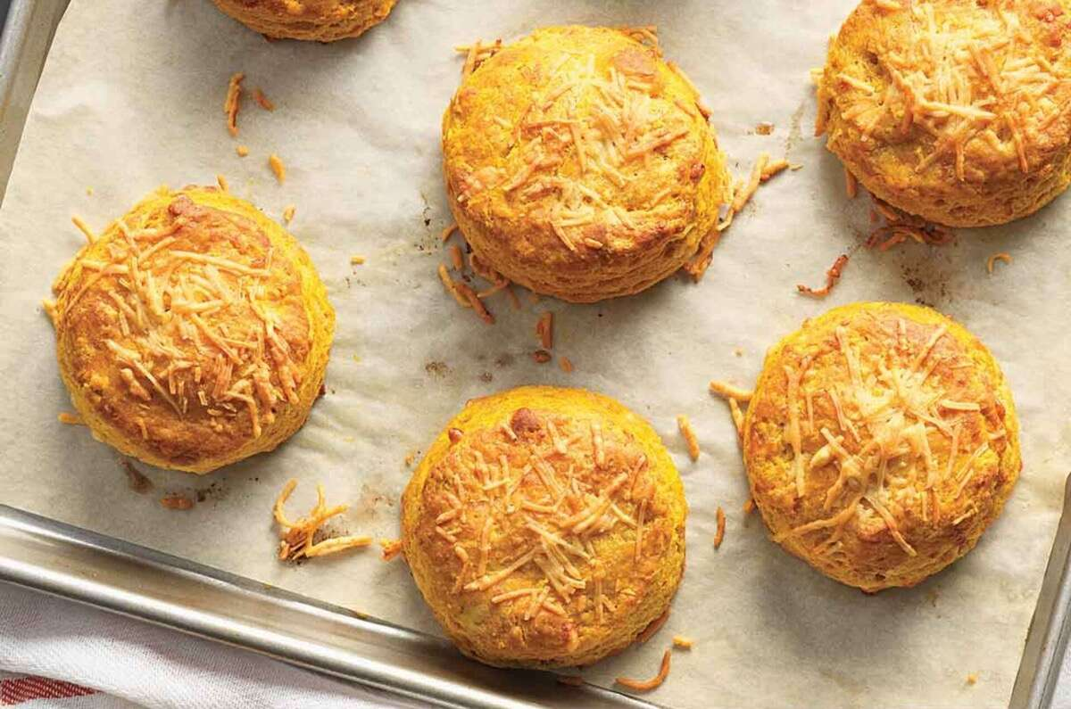 Bright gold pumpkin cheddar biscuits on a baking sheet.
