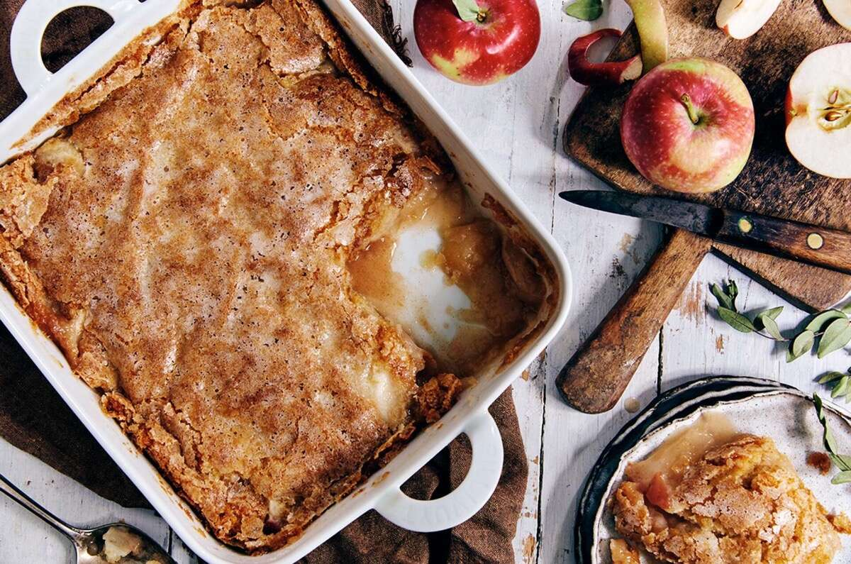 Sugar-crusted apple cobbler in a pan, some on a plate, apples on the table alongside.