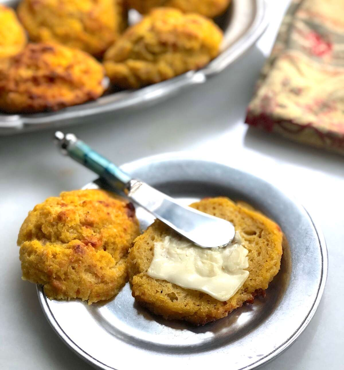 Pumpkin cheddar biscuit on a plate, spread with soft butter, more biscuits in the background.
