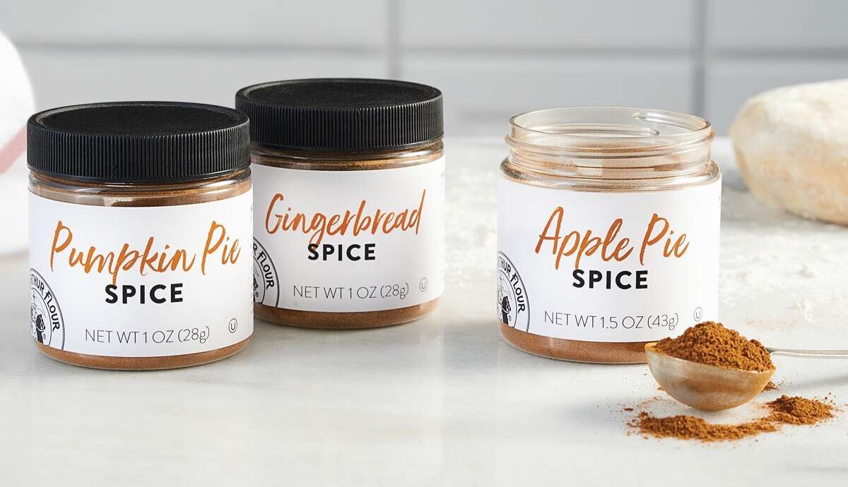 Three jars of spice on a white countertop: Apple Pie Spice, Pumpkin Pie Spice, and Gingerbread Spice