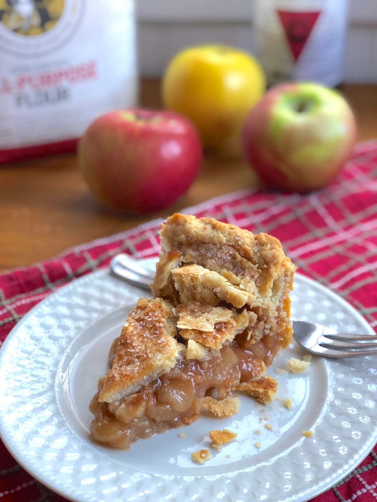 Slice of apple pie on a plate, apples in the background.