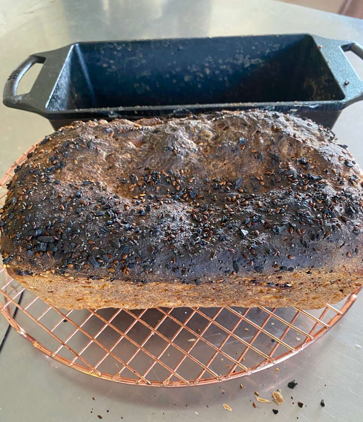 Loaf of bread burned on top in front of black cast iron loaf pan.