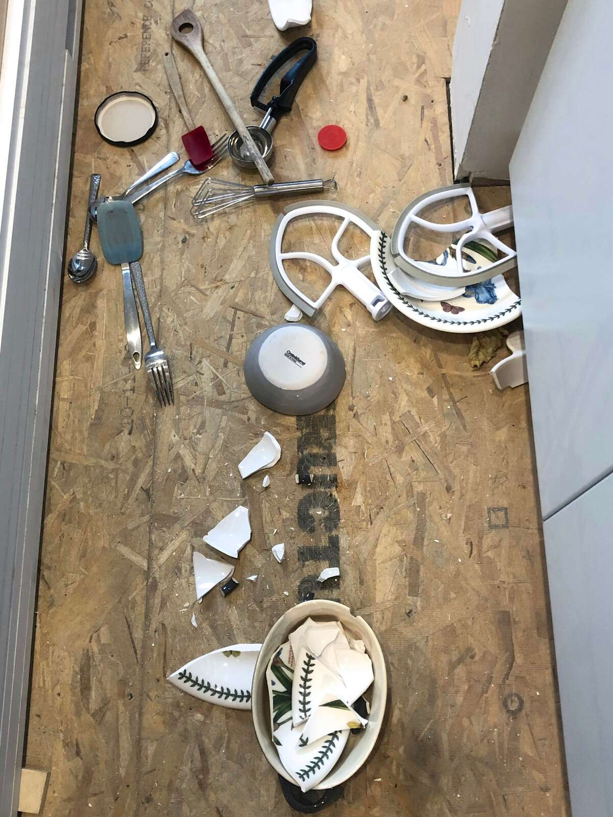 Kitchen floor with broken crockery, spilled silverware, and KitchenAid mixer attachments.