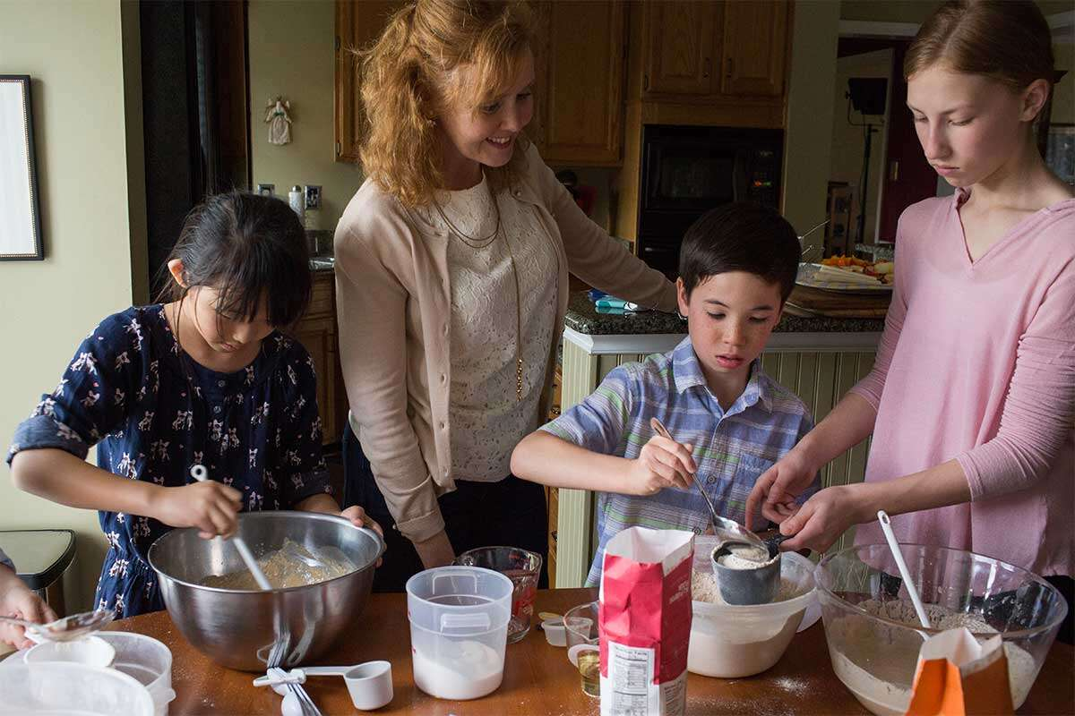 A mother surrounded by three children all baking together in the kitchen