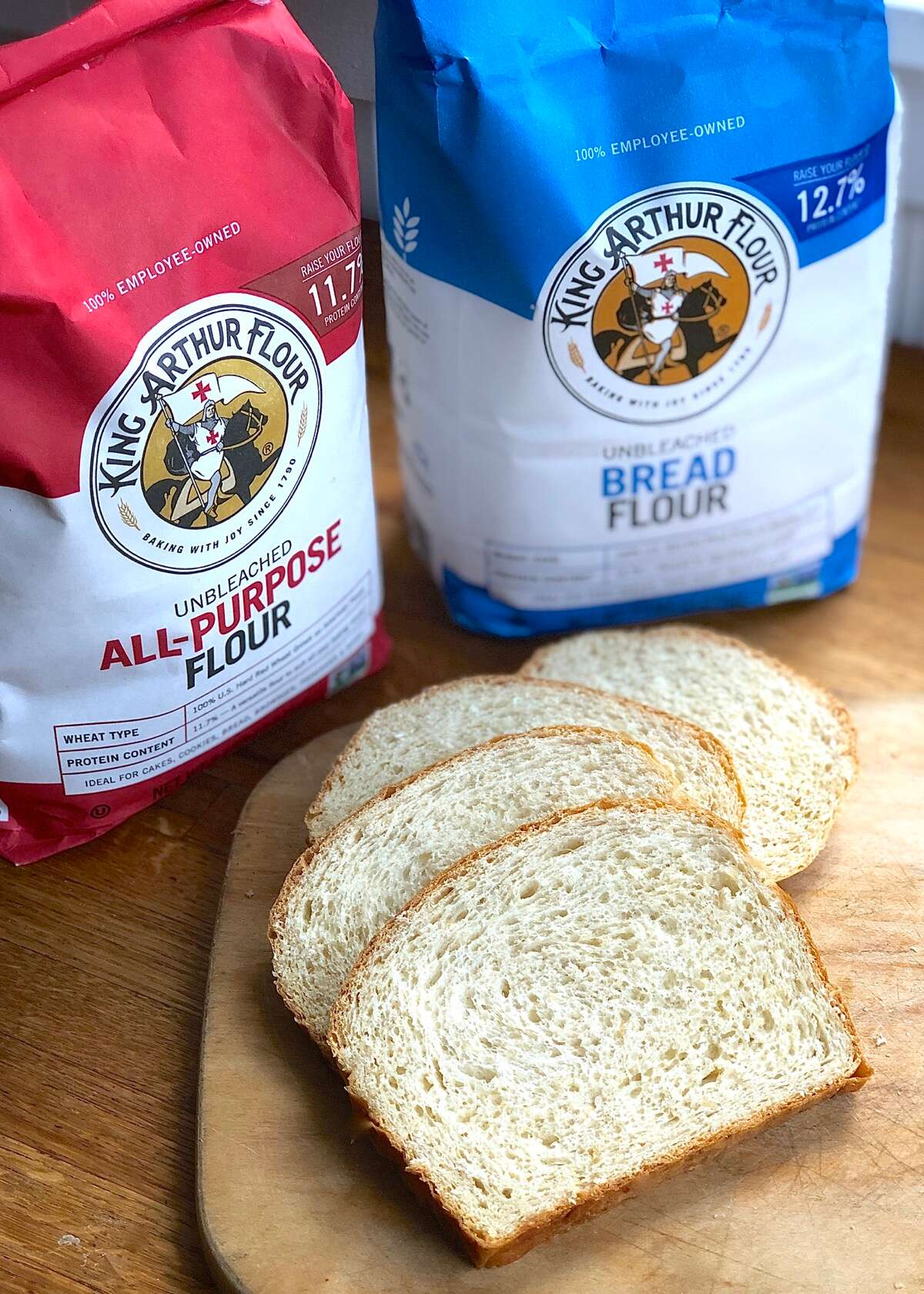 Bags of King Arthur all-purpose flour and bread flour, plus sliced oatmeal bread on a board