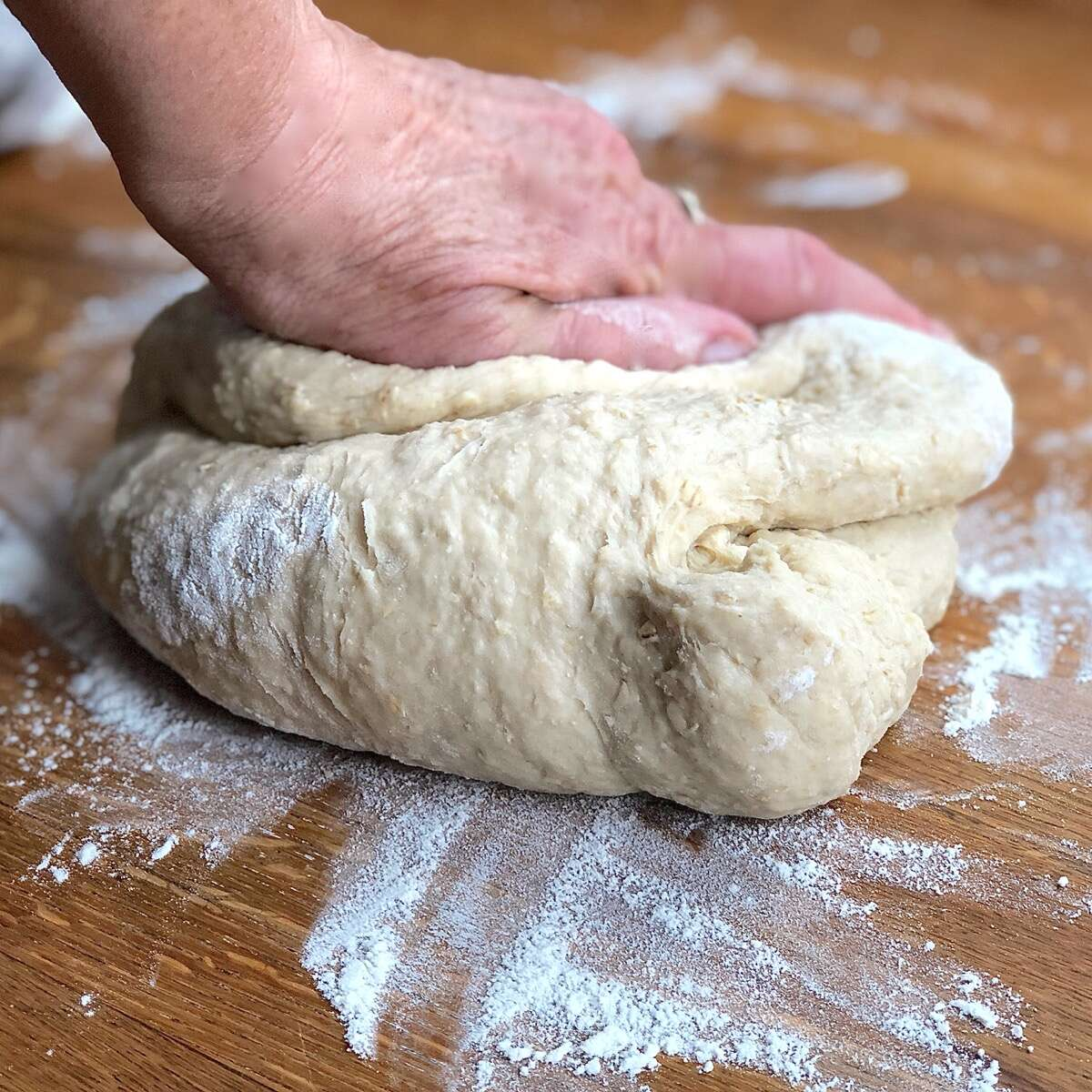 Hand-kneading oatmeal bread dough on a floured board
