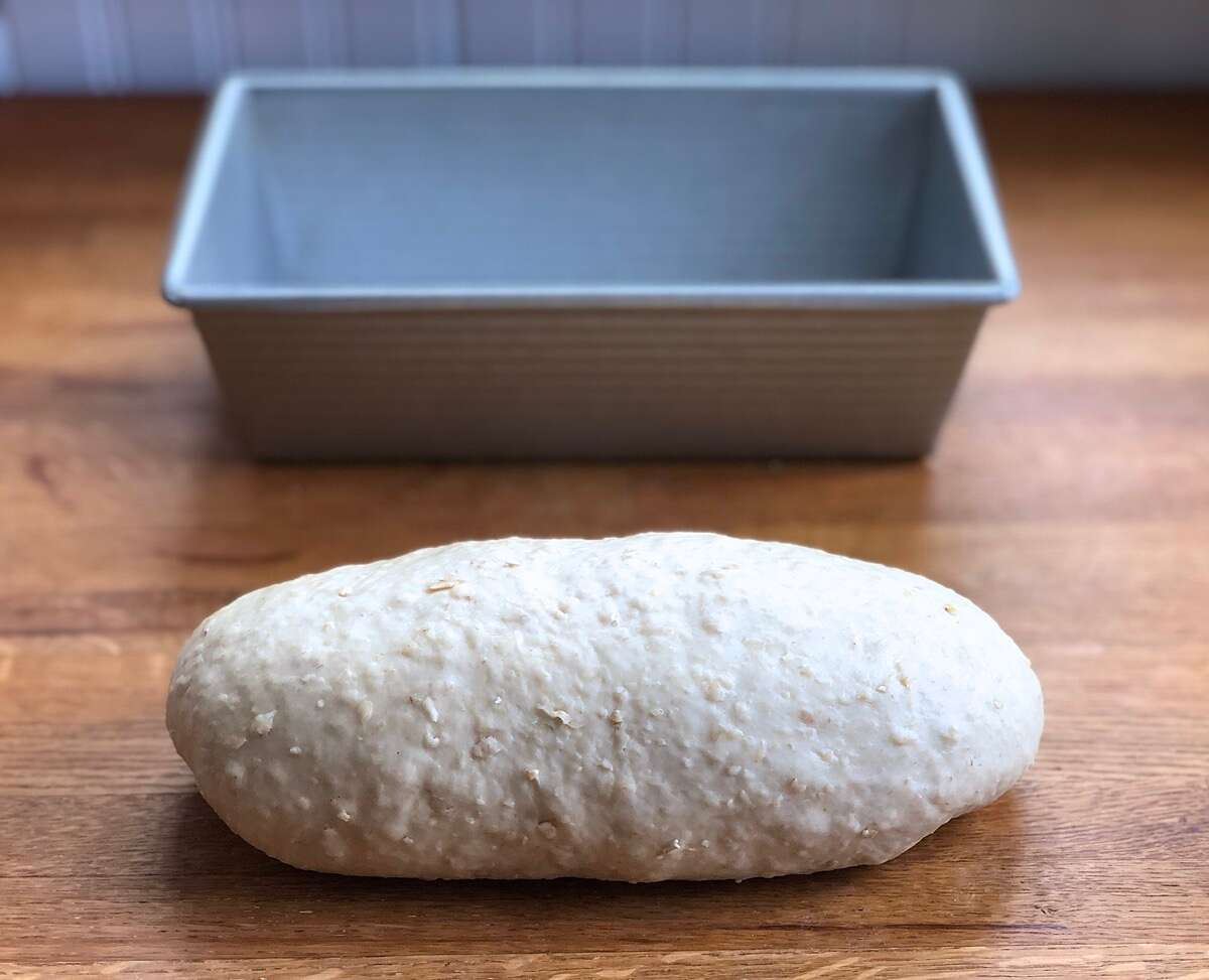 Oatmeal bread dough shaped into a log