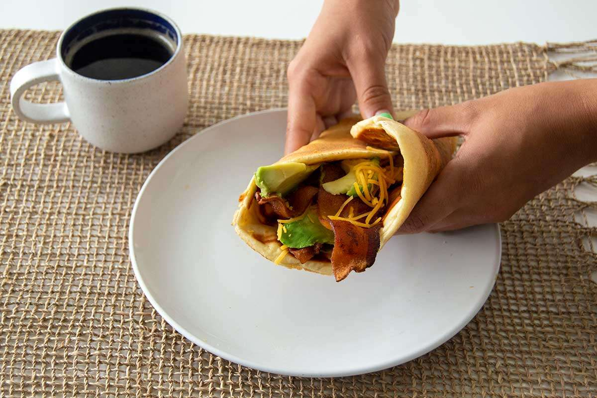 Hands holding bacon and avocado wrap, with a pancake as the flatbread