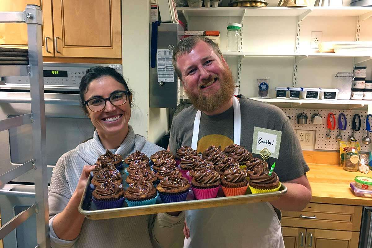 Two bakers holding up a tray of frosted cupcakes, smiling