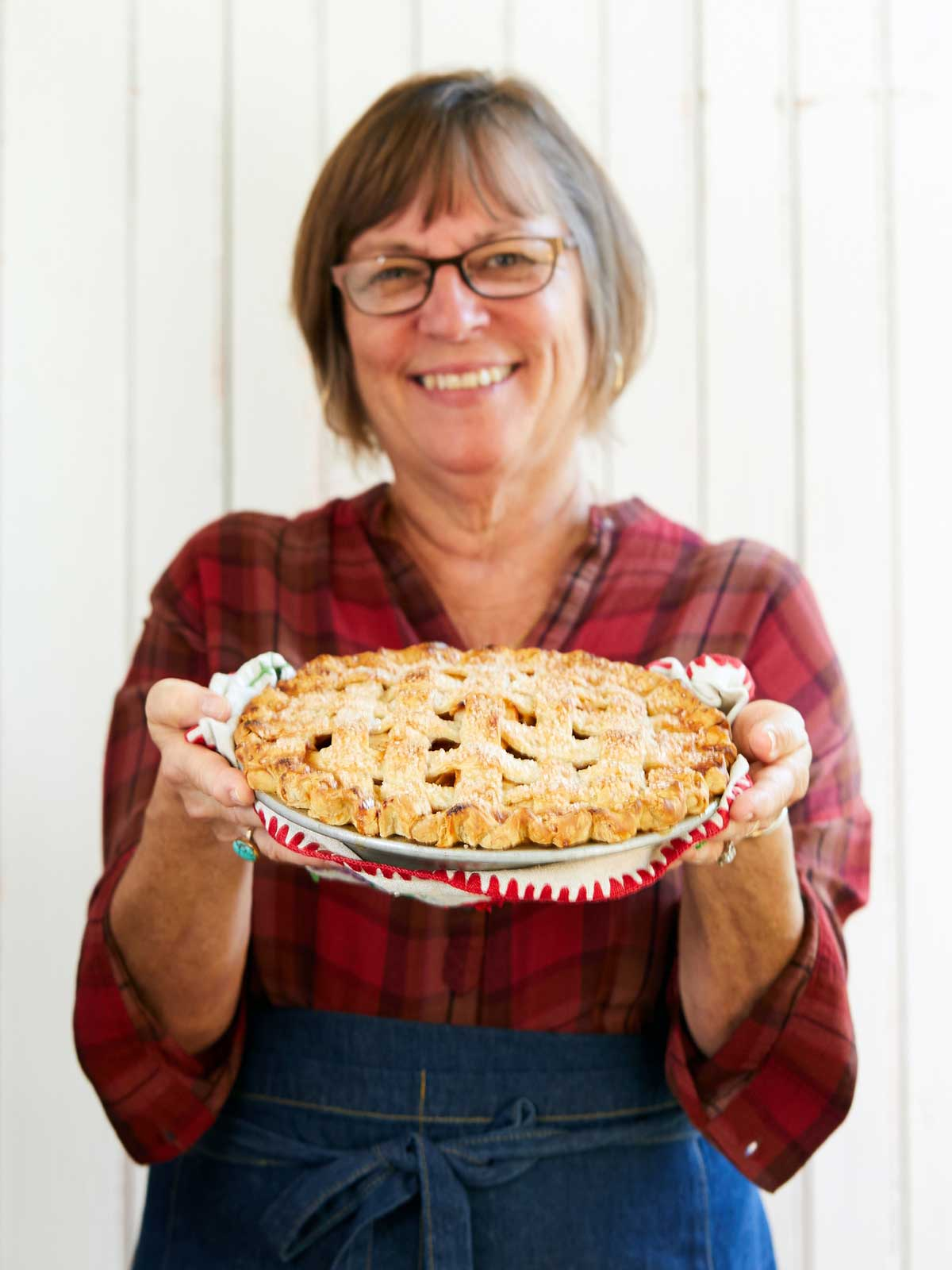 A woman holding out a lattice-topped apple pie, smiling