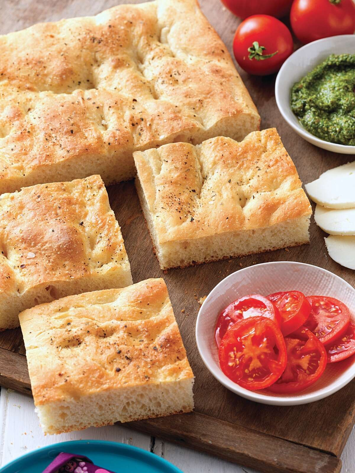 No-Fuss Focaccia cut into squares on a serving board with tomato, pesto, and mozzarella on the side.