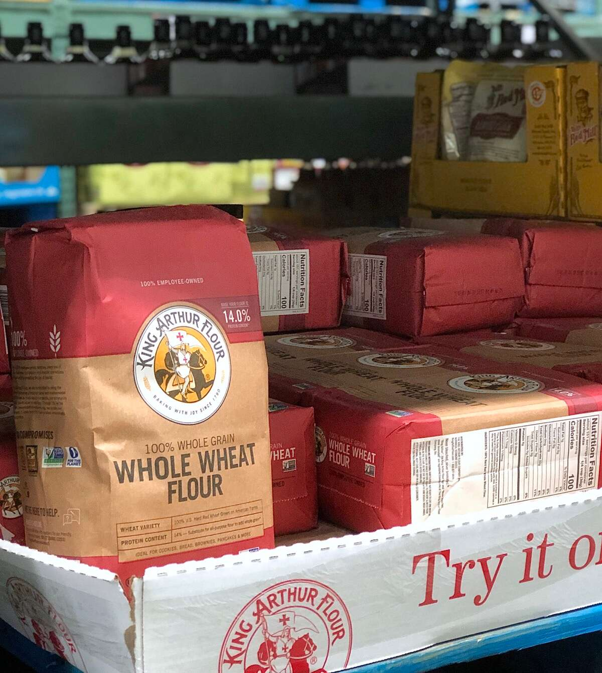 Bag of King Arthur Premium Whole Wheat Flour on the shelf of a warehouse store.