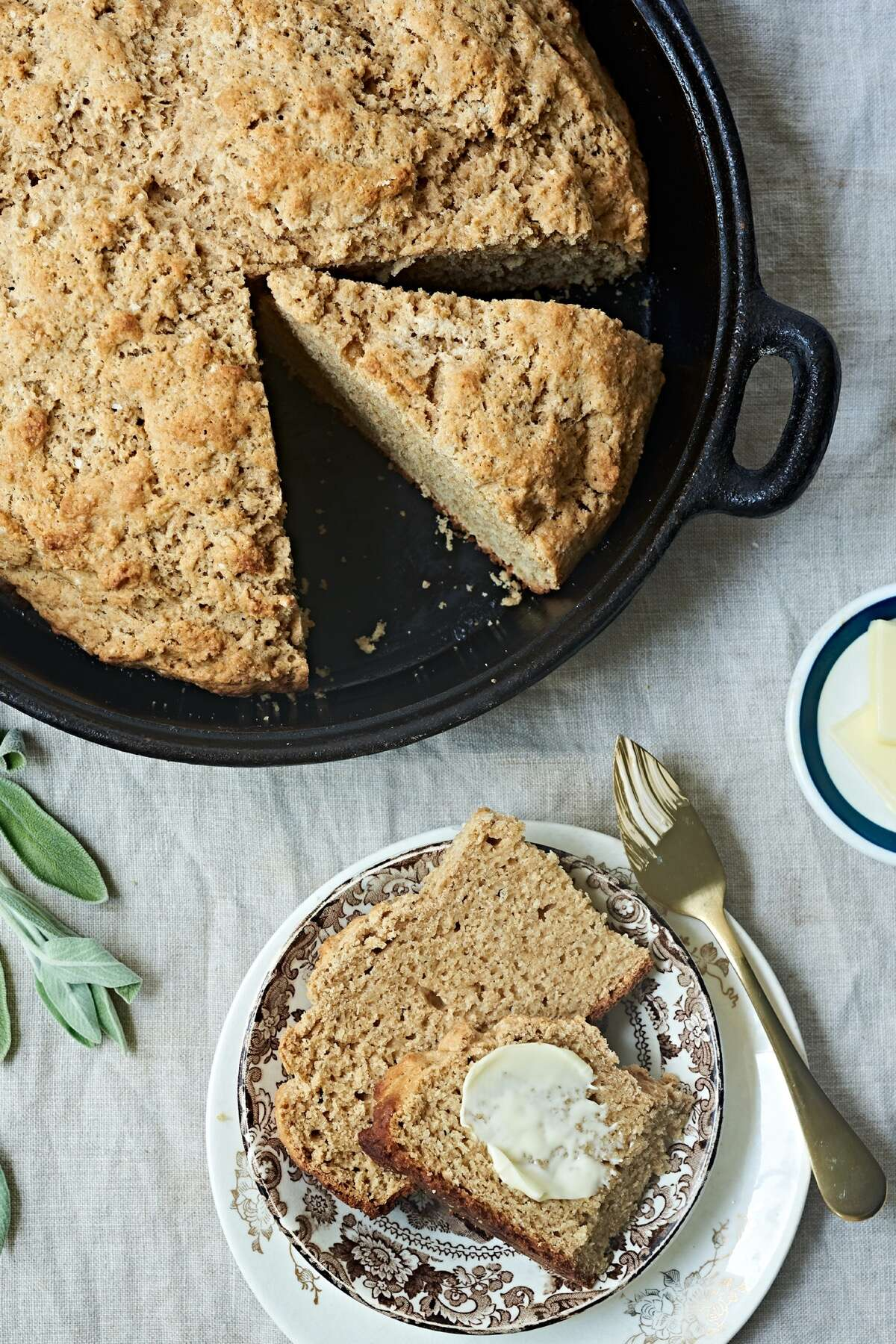 Irish Buttermilk Brown Bread baked in a cast iron pan, one wedge placed on a plate and buttered.