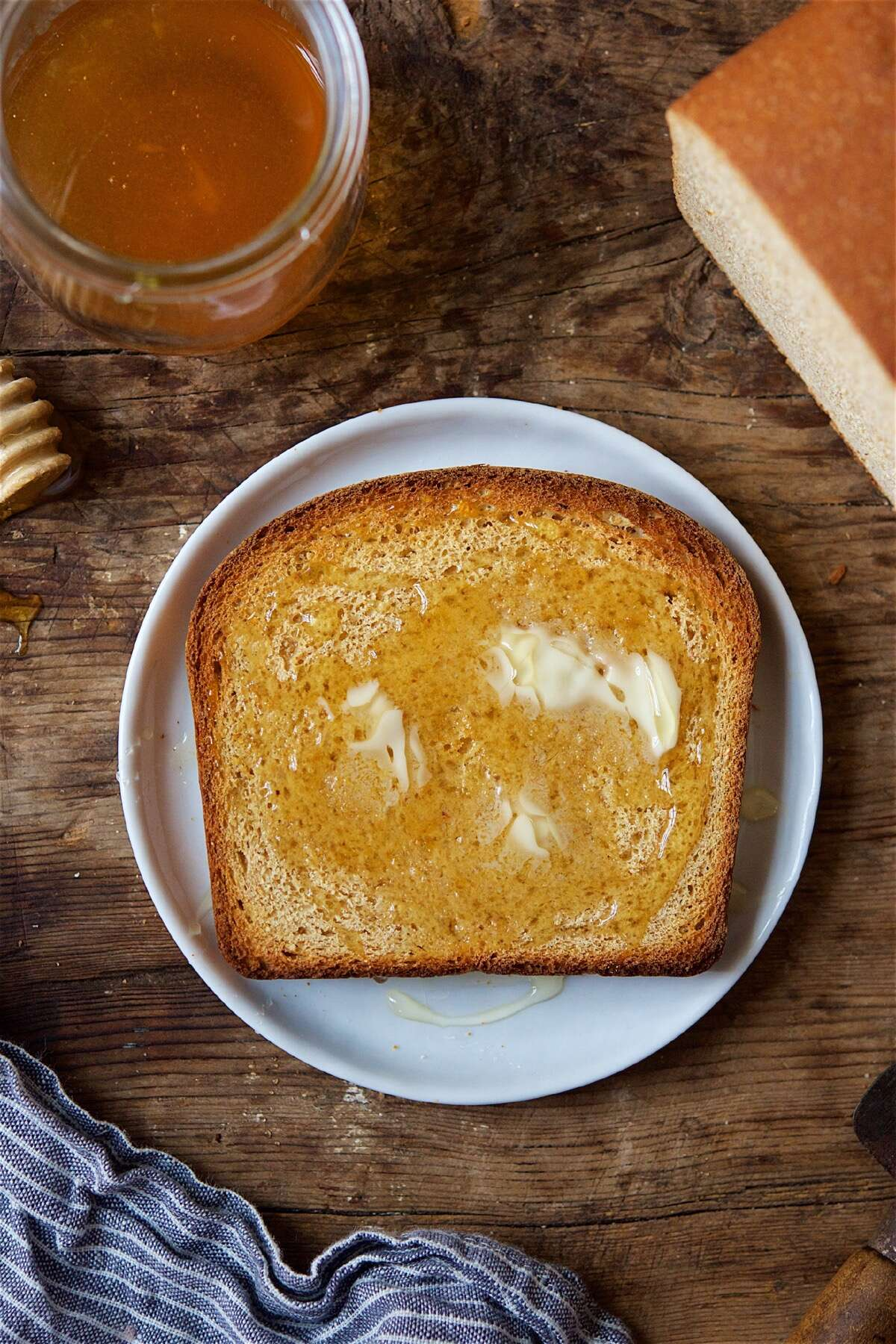 A slice of Classic 100% Whole Wheat Bread on a plate, lightly toasted and topped with melting butter and honey.