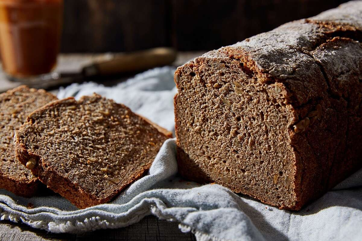 Loaf of Vollkornbrot, a dense, heavy rye bread, sliced on a cloth.