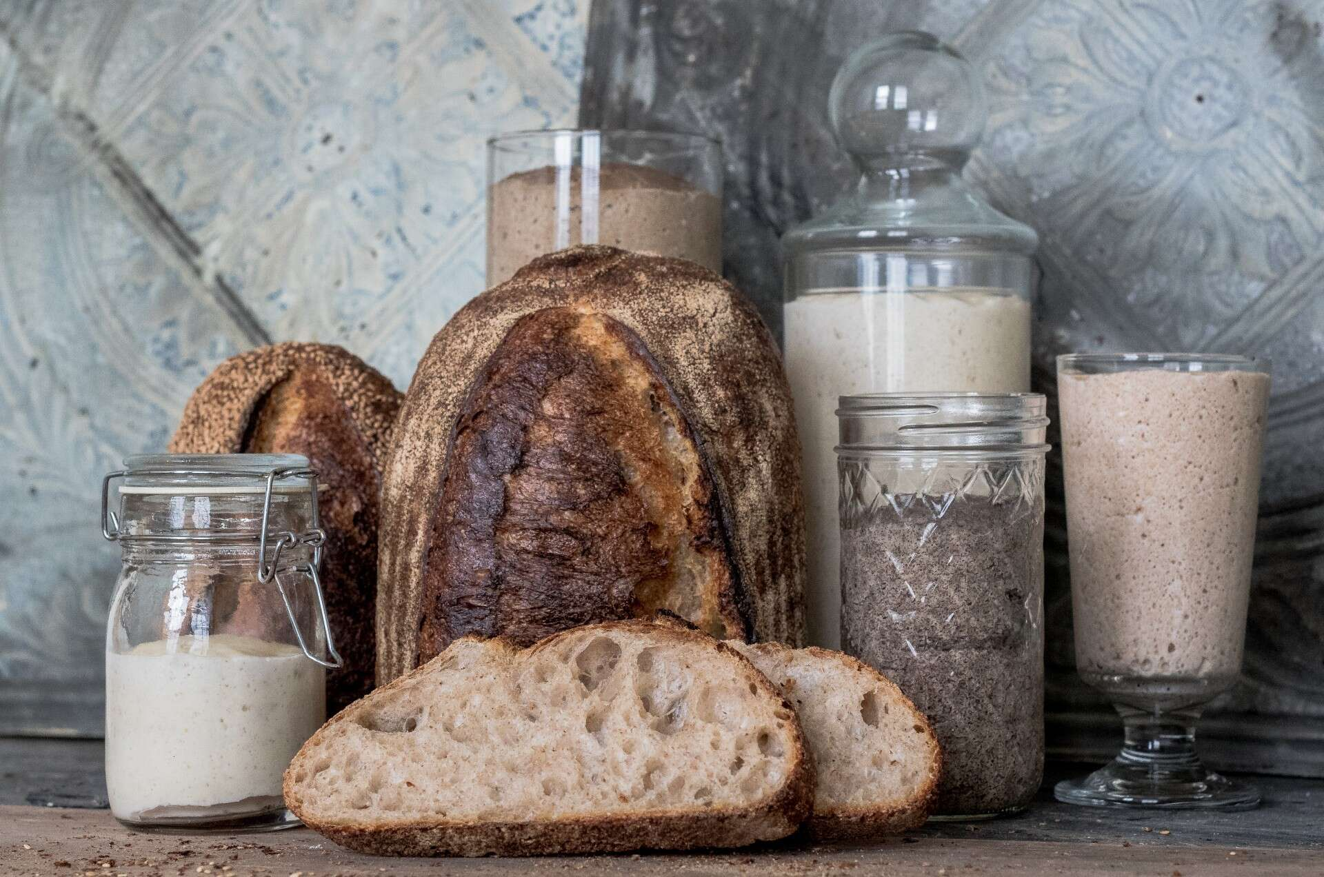 A series of preferments in jars on a table with bread