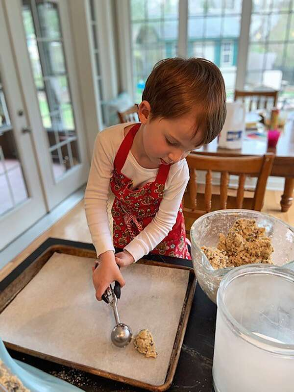A young baker using a cookie scoop to scoop dough onto a baking sheet