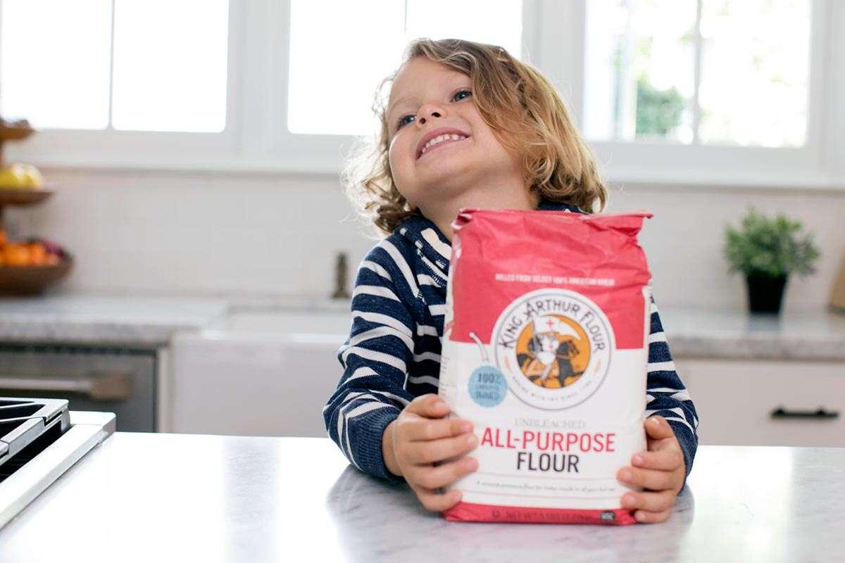 A small child smiling with a bag of flour in a kitchen