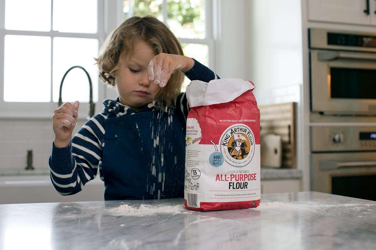 A child playing with King Arthur Flour on a kitchen counter
